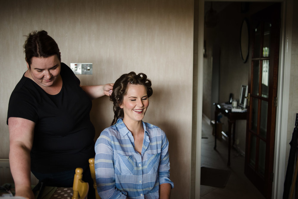 Bride smiles while getting hair styled on the morning of her wedding
