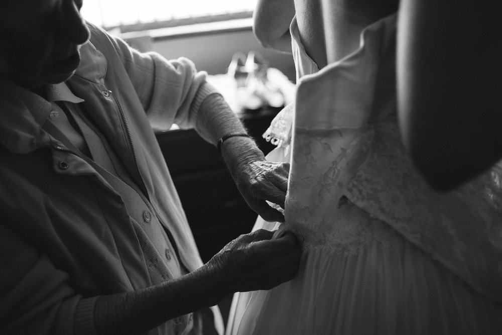 bride gets buttoned into dress on morning of wedding
