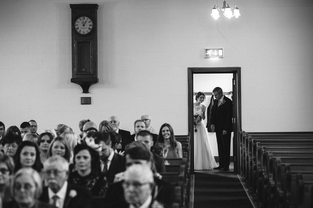 Bride peeks into church and waves before wedding, Randalstown Presbyterian Church, Northern Ireland