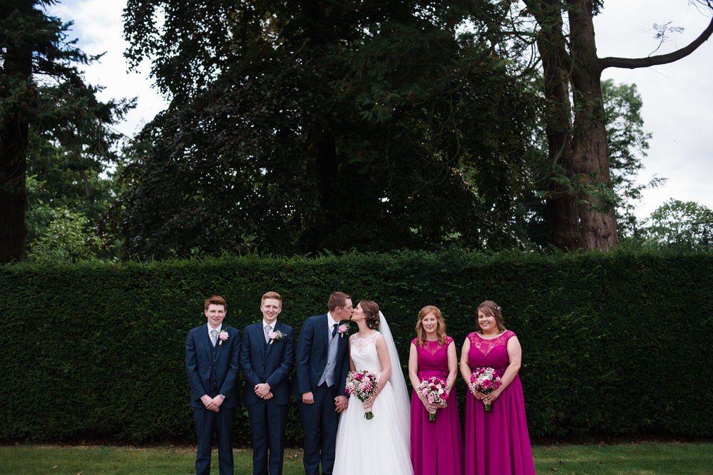 Bride and Groom kiss, with bridal party, Antrim Castle Gardens, Northern Ireland