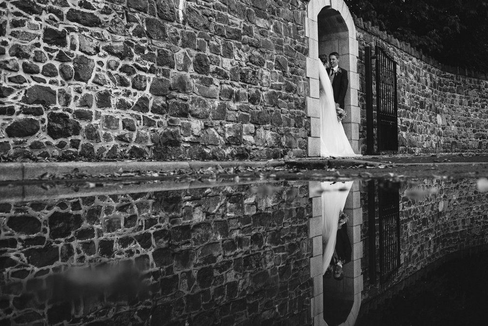 Bride and groom in arch reflection in puddle, Antrim Castle Gardens, Northern Ireland
