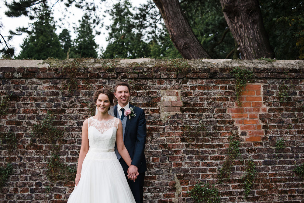 Bride and Groom in front of red brick wall, Antrim Castle Gardens, Northern Ireland