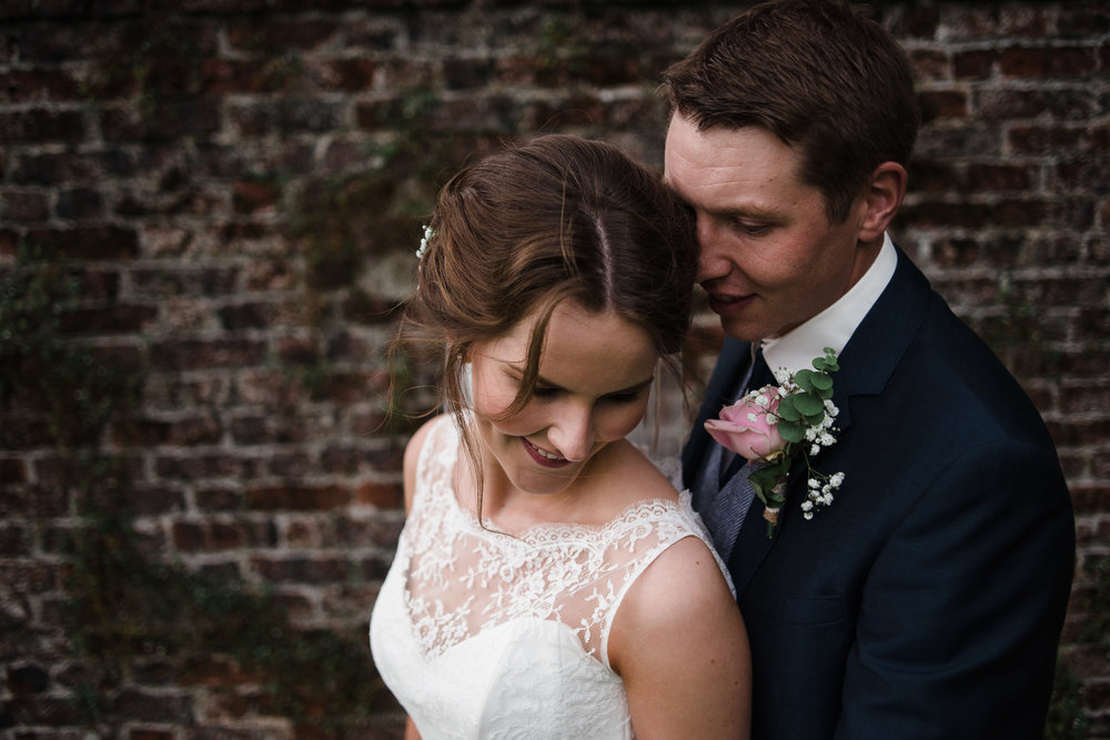 Bride and Groom embrace in front of red brick wall, Antrim Castle Gardens, Northern Ireland