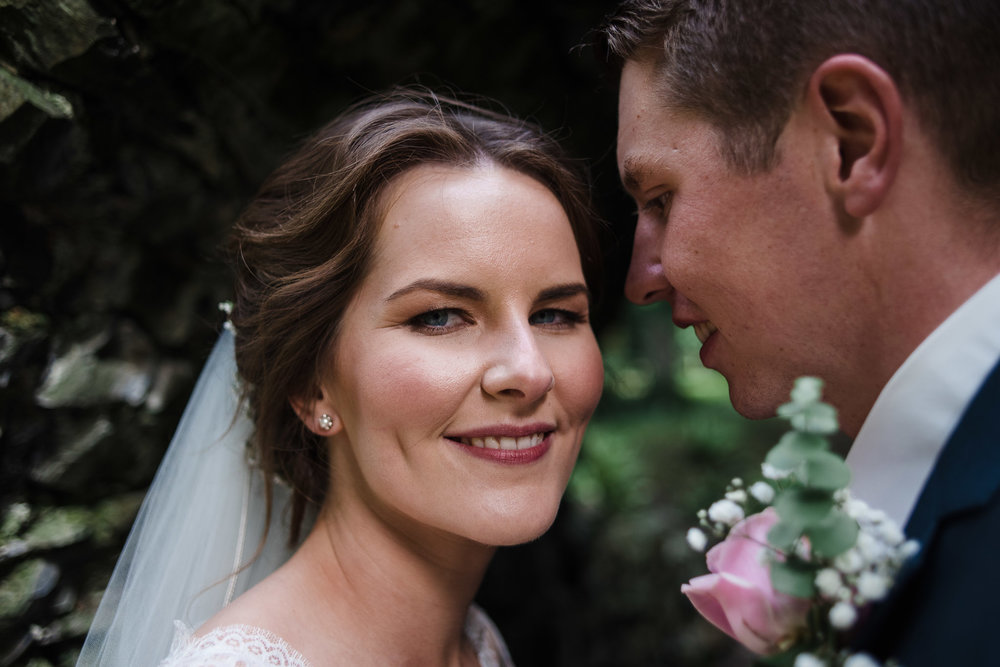 Bride looks at camera, while groom looks at bride, Antrim Castle Gardens, Northern Ireland