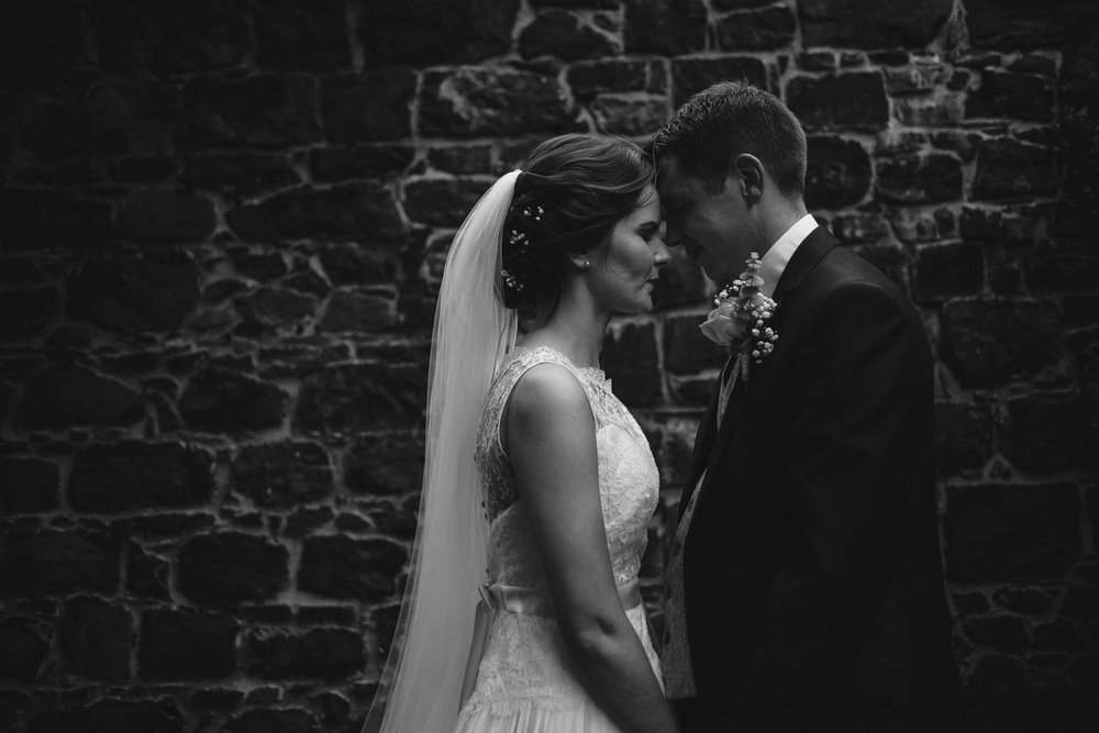 Bride and Groom lit by ray of light in front of stone wall, Antrim Castle Gardens, Northern Ireland