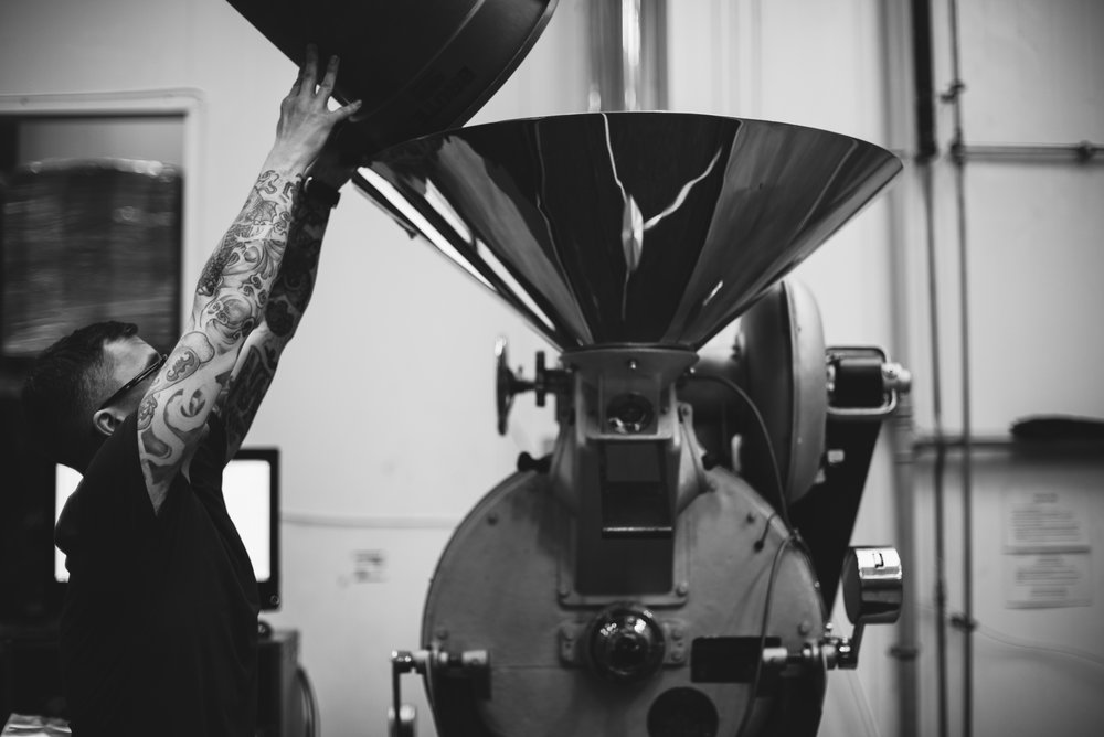 Roaster Stephen Houston pours green coffee beans in to a Probat Coffee Roaster